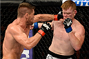 BANGOR, ME - AUGUST 16:  (L-R) Tom Watson punches Sam Alvey in their middleweight bout during the UFC fight night event at the Cross Insurance Center on August 16, 2014 in Bangor, Maine. (Photo by Jeff Bottari/Zuffa LLC/Zuffa LLC via Getty Images)