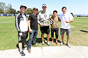 ALAMEDA, CA - AUGUST 26:  (L-R) Dan Marks, UFC bantamweight champion TJ Dillashaw Oakland Raiders head coach Dennis Allen, flyweight Joseph Benavidez and lightweight Gilbert Melendez interact at the Oakland Raiders training facility on August 26, 2014 in Alameda, California. (Photo by Jeff Bottari/Zuffa LLC/Zuffa LLC via Getty Images)