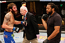 MASHANTUCKET, CT - SEPTEMBER 05:  (R-L) Referee Herb Dean calls the fight due to a cut to the head of Michael Chiesa between rounds against Joe Lauzon in their lightweight bout during the UFC Fight Night event at Foxwoods Resort Casino on September 5, 2014 in Mashantucket, Connecticut.  (Photo by Josh Hedges/Zuffa LLC/Zuffa LLC via Getty Images)