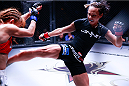 Michelle Waterson delivers a body kick during her atomweight title defense at Invicta FC 8. (Photos by Esther Lin/INVICTA FC.)