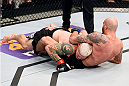 PHOENIX, AZ - DECEMBER 13:  (L-R) Joe Riggs injures his neck as he takes down Ben Saunders in their welterweight fight during the UFC Fight Night event at the U.S. Airways Center on December 13, 2014 in Phoenix, Arizona.  (Photo by Josh Hedges/Zuffa LLC/Zuffa LLC via Getty Images)