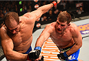 PHOENIX, AZ - DECEMBER 13:  (R-L) Stipe Miocic punches Junior Dos Santos of Brazil in their heavyweight fight during the UFC Fight Night event at the U.S. Airways Center on December 13, 2014 in Phoenix, Arizona.  (Photo by Josh Hedges/Zuffa LLC/Zuffa LLC via Getty Images)
