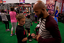 LAS VEGAS, NEVADA - JANUARY 28: UFC flyweight champion Demetrious Johnson helps a young boy wrap his hands while visiting the UFC Gym in Green Valley. (Photo by Brandon Magnus/Zuffa LLC/Zuffa LLC)