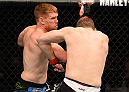 ADELAIDE, AUSTRALIA - MAY 10:   (L-R) Sam Alvey punches Daniel Kelly in their middleweight bout during the UFC Fight Night event at the Adelaide Entertainment Centre on May 10, 2015 in Adelaide, Australia. (Photo by Josh Hedges/Zuffa LLC/Zuffa LLC via Getty Images)