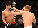 ADELAIDE, AUSTRALIA - MAY 10:   (R-L) Daniel Hooker punches Hatsu Hioki in their featherweight bout during the UFC Fight Night event at the Adelaide Entertainment Centre on May 10, 2015 in Adelaide, Australia. (Photo by Josh Hedges/Zuffa LLC/Zuffa LLC via Getty Images)