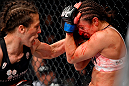 BERLIN, GERMANY - JUNE 20:   (L-R) Joanna Jedrzejczyk of Poland punches Jessica Penne of the United States in their women's strawweight championship bout during the UFC Fight Night event at the O2 World on June 20, 2015 in Berlin, Germany. (Photo by Josh Hedges/Zuffa LLC/Zuffa LLC via Getty Images)