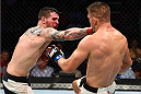 NASHVILLE, TN - AUGUST 08:  (L-R) Chris Camozzi punches Tom Watson of England in their middleweight bout during the UFC Fight Night event at Bridgestone Arena on August 8, 2015 in Nashville, Tennessee.  (Photo by Josh Hedges/Zuffa LLC/Zuffa LLC via Getty Images)