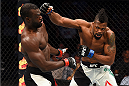 NASHVILLE, TN - AUGUST 08:  (R-L) Oluwale Bamgbose punches Uriah Hall of Jamaica in their middleweight bout during the UFC Fight Night event at Bridgestone Arena on August 8, 2015 in Nashville, Tennessee.  (Photo by Josh Hedges/Zuffa LLC/Zuffa LLC via Getty Images)