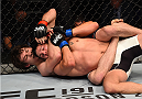 SASKATOON, SK - AUGUST 23:  (L-R) Olivier Aubin-Mercier attempts to secure a rear choke submission against Tony Sims of the United States in their lightweight bout during the UFC event at the SaskTel Centre on August 23, 2015 in Saskatoon, Saskatchewan, Canada. (Photo by Jeff Bottari/Zuffa LLC/Zuffa LLC via Getty Images)