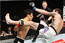 SAITAMA, JAPAN - SEPTEMBER 27: Takeya Mizugaki of Japan goes for a takedown on George Roop of the United States of America in their bantamweight bout during the UFC event at the Saitama Super Arena on September 27, 2015 in Saitama, Japan. (Photo by Mitch Viquez/Zuffa LLC/Zuffa LLC via Getty Images)