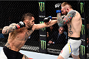 LAS VEGAS, NEVADA - DECEMBER 10:  (L) Santiago Ponzinibbio punches Andreas Stahl in their welterweight bout during the UFC Fight Night event at The Chelsea at the Cosmopolitan of Las Vegas on December 10, 2015 in Las Vegas, Nevada.  (Photo by Jeff Bottari/Zuffa LLC/Zuffa LLC via Getty Images)