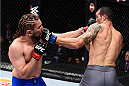 LAS VEGAS, NV - DECEMBER 11: (L-R) Chris Gruetzemacher punches Abner Lloveras in their lightweight bout during the TUF Finale event inside The Chelsea at The Cosmopolitan of Las Vegas on December 11, 2015 in Las Vegas, Nevada.  (Photo by Jeff Bottari/Zuffa LLC/Zuffa LLC via Getty Images) *** Local Caption *** Chris Gruetzemacher; Abner Lloveras