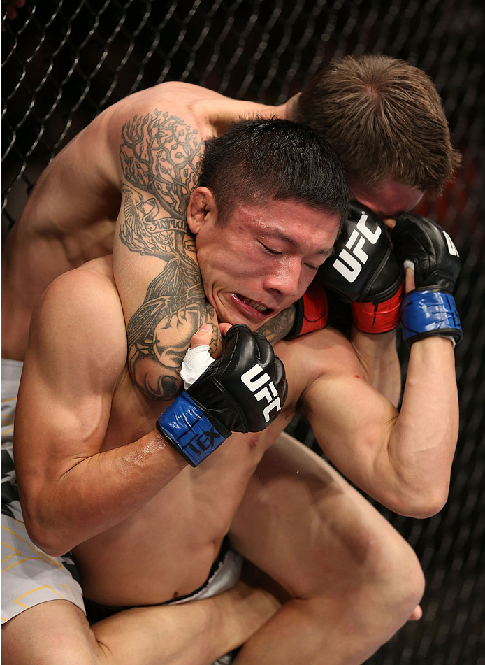 HOUSTON, TEXAS - OCTOBER 19:  Dustin Pague (top) attempts a choke submission on Kyoji Horiguchi in their UFC bantamweight bout at the Toyota Center on October 19, 2013 in Houston, Texas. (Photo by Nick Laham/Zuffa LLC/Zuffa LLC via Getty Images)