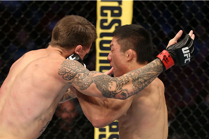 HOUSTON, TEXAS - OCTOBER 19:  (R-L) Kyoji Horiguchi lands a left punch to the head of Dustin Pague in their UFC bantamweight bout at the Toyota Center on October 19, 2013 in Houston, Texas. (Photo by Nick Laham/Zuffa LLC/Zuffa LLC via Getty Images)