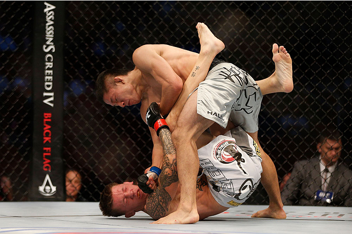 HOUSTON, TEXAS - OCTOBER 19:  Kyoji Horiguchi (top) punches Dustin Pague in their UFC bantamweight bout at the Toyota Center on October 19, 2013 in Houston, Texas. (Photo by Josh Hedges/Zuffa LLC/Zuffa LLC via Getty Images)