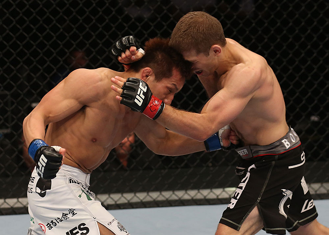 DENVER, CO - AUGUST 11:  (L-R) Eiji Mitsuoka punches to the body of Nik Lentz during their featherweight bout at UFC 150 inside Pepsi Center on August 11, 2012 in Denver, Colorado. (Photo by Nick Laham/Zuffa LLC/Zuffa LLC via Getty Images)