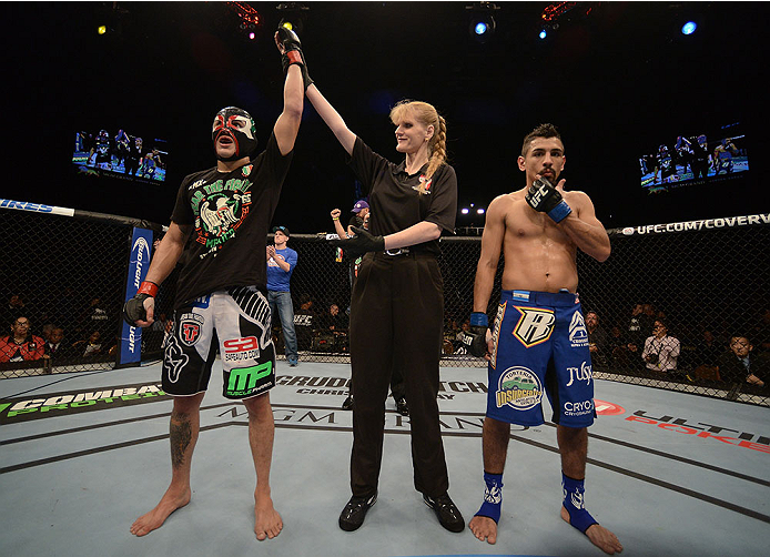 LAS VEGAS, NV - NOVEMBER 16:  Erik Perez (left) is declared the winner over Edwin Figueroa (right) in their bantamweight bout during the UFC 167 event inside the MGM Grand Garden Arena on November 16, 2013 in Las Vegas, Nevada. (Photo by Donald Miralle/Zuffa LLC/Zuffa LLC via Getty Images) *** Local Caption *** Erik Perez; Edwin Figueroa