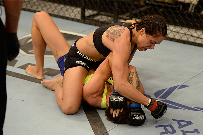 Amanda Nunes (top) punches Germaine de Randamie in their UFC women's bantamweight bout on November 6, 2013 in Fort Campbell, KY. (Photo by Jeff Bottari/Zuffa LLC)