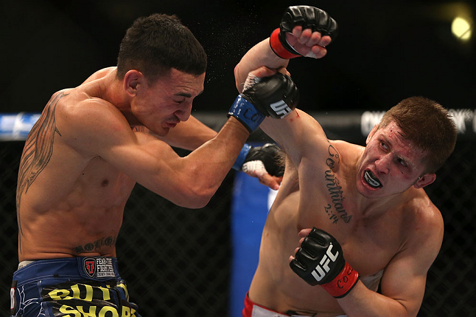 DENVER, CO - AUGUST 11:  (R-L) Justin Lawrence punches Max Holloway during their featherweight bout at UFC 150 inside Pepsi Center on August 11, 2012 in Denver, Colorado. (Photo by Josh Hedges/Zuffa LLC/Zuffa LLC via Getty Images)