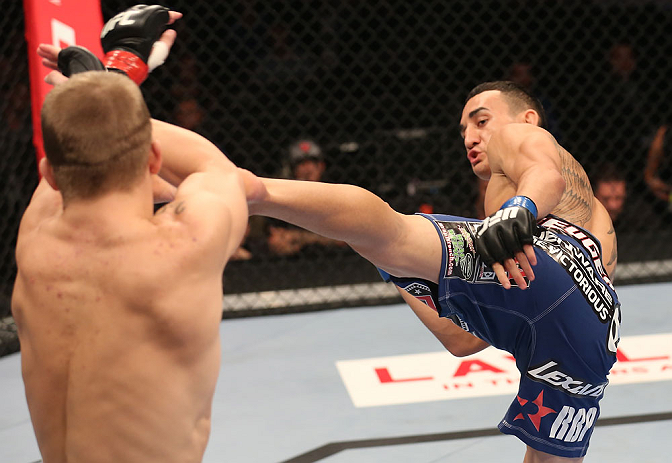 DENVER, CO - AUGUST 11:  (R-L) Max Holloway kicks Justin Lawrence during their featherweight bout at UFC 150 inside Pepsi Center on August 11, 2012 in Denver, Colorado. (Photo by Nick Laham/Zuffa LLC/Zuffa LLC via Getty Images)