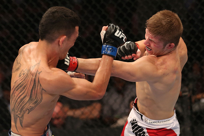 DENVER, CO - AUGUST 11:  (L-R) Justin Lawrence punches Max Holloway during their featherweight bout at UFC 150 inside Pepsi Center on August 11, 2012 in Denver, Colorado. (Photo by Nick Laham/Zuffa LLC/Zuffa LLC via Getty Images)