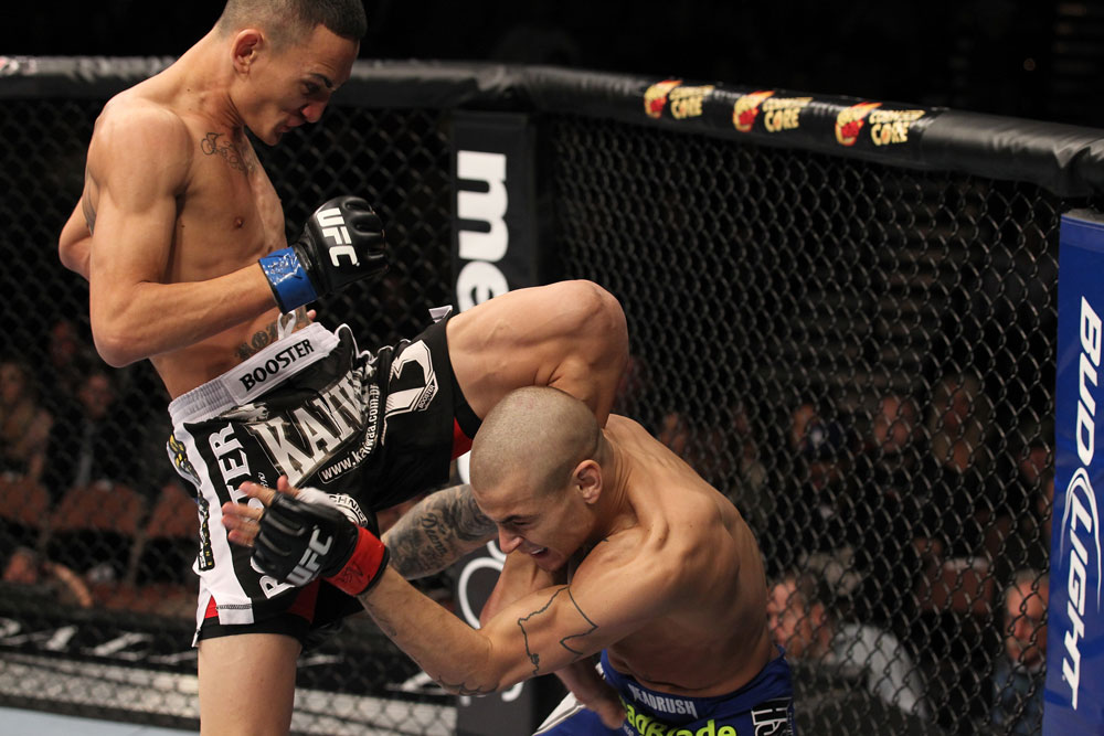 LAS VEGAS, NV - FEBRUARY 04:  Max Holloway (black shorts) delivers a knee to Dustin Poirier during the UFC 143 event at Mandalay Bay Events Center on February 4, 2012 in Las Vegas, Nevada.  (Photo by Nick Laham/Zuffa LLC/Zuffa LLC via Getty Images) *** Local Caption *** Max Holloway; Dustin Poirier