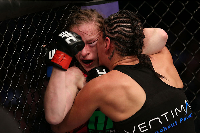 HOUSTON, TEXAS - OCTOBER 19:  (L-R) Sarah Kaufman gets pushed into the cage by Jessica Eye in their UFC women's bantamweight bout at the Toyota Center on October 19, 2013 in Houston, Texas. (Photo by Nick Laham/Zuffa LLC/Zuffa LLC via Getty Images)