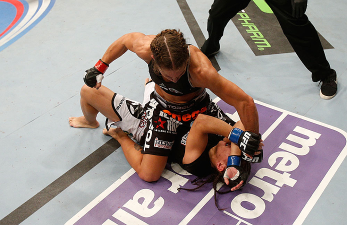 SEATTLE, WA - JULY 27: Liz Carmouche (top) punches Jessica Andrade in their bantamweight bout during the UFC on FOX event at Key Arena on July 27, 2013 in Seattle, Washington. (Photo by Josh Hedges/Zuffa LLC/Zuffa LLC via Getty Images) *** Local Caption *** Liz Carmouche; Jessica Andrade
