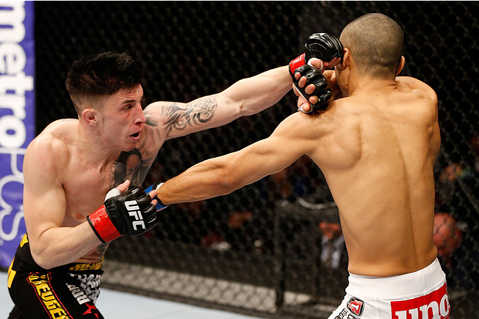 MANCHESTER, ENGLAND - OCTOBER 26:  (L-R) Norman Parke punches Jon Tuck in their lightweight bout during the UFC Fight Night event at Phones 4 U Arena on October 26, 2013 in Manchester, England. (Photo by Josh Hedges/Zuffa LLC/Zuffa LLC via Getty Images)
