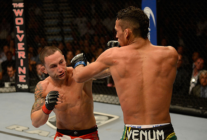 LAS VEGAS, NV - JULY 06:  (L-R) Frankie Edgar punches Charles Oliveira in their featherweight fight during the UFC 162 event inside the MGM Grand Garden Arena on July 6, 2013 in Las Vegas, Nevada.  (Photo by Donald Miralle/Zuffa LLC/Zuffa LLC via Getty Images) *** Local Caption *** Frankie Edgar; Charles Oliveira