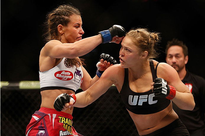 LAS VEGAS, NV - DECEMBER 28:  (L-R) Miesha Tate and Ronda Rousey exchange punches in their UFC women's bantamweight championship bout during the UFC 168 event at the MGM Grand Garden Arena on December 28, 2013 in Las Vegas, Nevada. (Photo by Josh Hedges/Zuffa LLC/Zuffa LLC via Getty Images) *** Local Caption *** Ronda Rousey; Miesha Tate