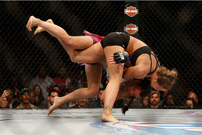 LAS VEGAS, NV - DECEMBER 28:  Ronda Rousey (black shorts) throws Miesha Tate in their UFC women's bantamweight championship bout during the UFC 168 event at the MGM Grand Garden Arena on December 28, 2013 in Las Vegas, Nevada. (Photo by Josh Hedges/Zuffa LLC/Zuffa LLC via Getty Images) *** Local Caption *** Ronda Rousey; Miesha Tate