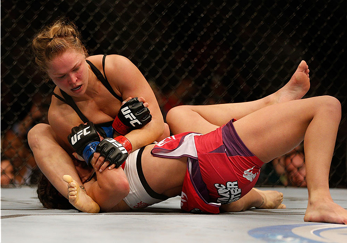LAS VEGAS, NV - DECEMBER 28:  Ronda Rousey (top) attempts to submit Miesha Tate in their UFC women's bantamweight championship bout during the UFC 168 event at the MGM Grand Garden Arena on December 28, 2013 in Las Vegas, Nevada. (Photo by Josh Hedges/Zuffa LLC/Zuffa LLC via Getty Images) *** Local Caption *** Ronda Rousey; Miesha Tate