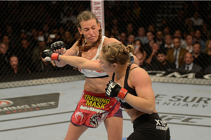 LAS VEGAS, NV - DECEMBER 28:  Ronda Rousey (black) punches Miesha Tate in their UFC women's bantamweight championship bout during the UFC 168 event at the MGM Grand Garden Arena on December 28, 2013 in Las Vegas, Nevada. (Photo by Donald Miralle/Zuffa LLC/Zuffa LLC via Getty Images) *** Local Caption *** Ronda Rousey; Miesha Tate