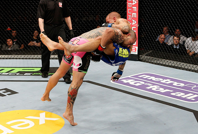 LONDON, ENGLAND - FEBRUARY 16:  (L-R) Cub Swanson takes down Dustin Poirier in their featherweight fight during the UFC on Fuel TV event on February 16, 2013 at Wembley Arena in London, England.  (Photo by Josh Hedges/Zuffa LLC/Zuffa LLC via Getty Images)