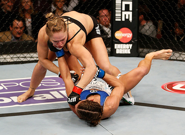 ANAHEIM, CA - FEBRUARY 23:  Ronda Rousey (top) punches Liz Carmouche in their women's bantamweight title fight during UFC 157 at Honda Center on February 23, 2013 in Anaheim, California.  (Photo by Josh Hedges/Zuffa LLC/Zuffa LLC via Getty Images) *** Local Caption *** Ronda Rousey; Liz Carmouche