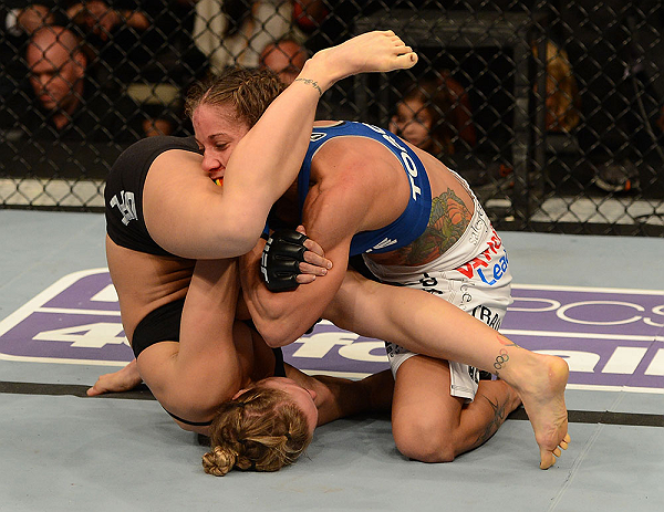 Carmouche grapples with Ronda Rousey during their championship fight at UFC 157
