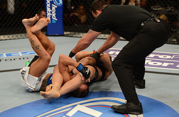 ANAHEIM, CA - FEBRUARY 23:  Ronda Rousey (center) attempts to submit Liz Carmouche in their women's bantamweight title fight during UFC 157 at Honda Center on February 23, 2013 in Anaheim, California.  (Photo by Donald Miralle/Zuffa LLC/Zuffa LLC via Getty Images) *** Local Caption *** Ronda Rousey; Liz Carmouche