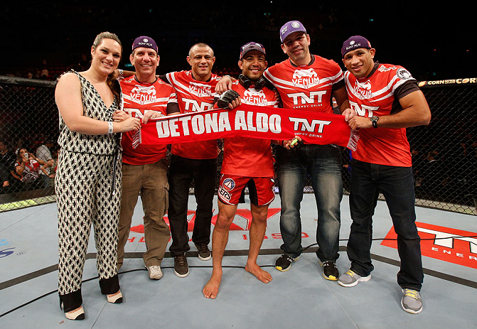 "RIO DE JANEIRO, BRAZIL - AUGUST 03:  Jose Aldo (third from right) poses with his team and wife after his victory over ""The Korean Zombie"" Chan Sung Jung in their featherweight championship bout during UFC 163 at HSBC Arena on August 3, 2013 in Rio de Janeiro, Brazil. (Photo by Josh Hedges/Zuffa LLC/Zuffa LLC via Getty Images)"