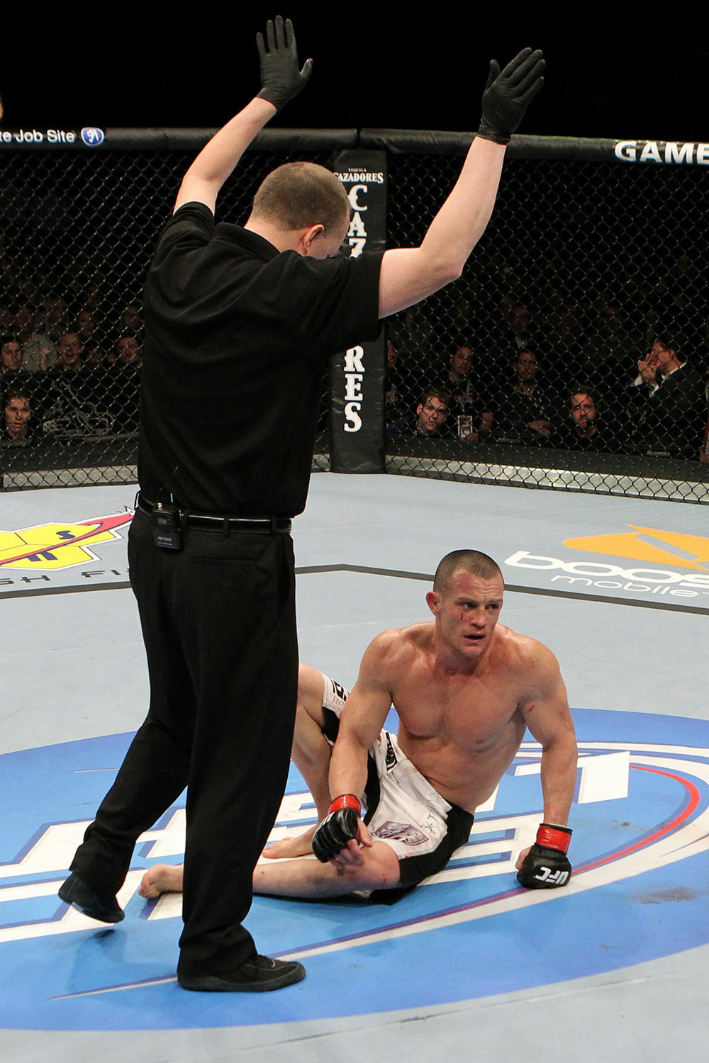 The referee calls the fight as Darren Elkins reacts after he lost by TKO against Edson Elkins.