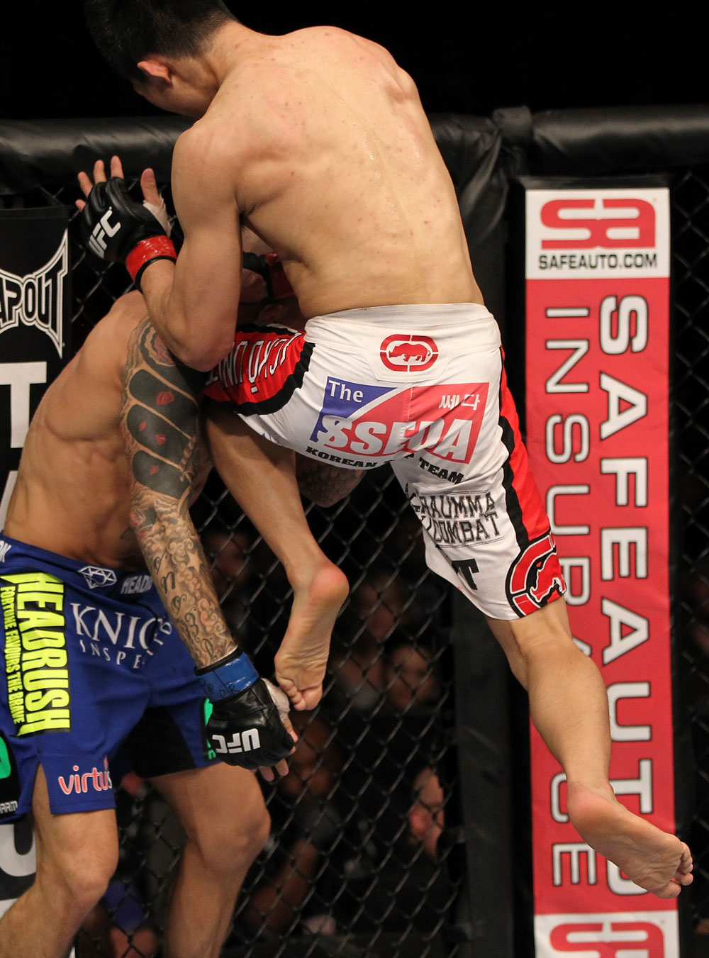 "FAIRFAX, VA - MAY 15:  (R-L) ""The Korean Zombie"" Chan Sung Jung lands a flying knee against Dustin Poirier in a featherweight bout during the UFC on Fuel TV event at Patriot Center on May 15, 2012 in Fairfax, Virginia.  (Photo by Josh Hedges/Zuffa LLC/Zuffa LLC via Getty Images)"