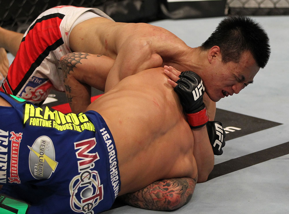 "FAIRFAX, VA - MAY 15:  (L-R) ""The Korean Zombie"" Chan Sung Jung defeats Dustin Poirier with a d'arce choke submission in a featherweight bout during the UFC on Fuel TV event at Patriot Center on May 15, 2012 in Fairfax, Virginia.  (Photo by Josh Hedges/Zuffa LLC/Zuffa LLC via Getty Images)"