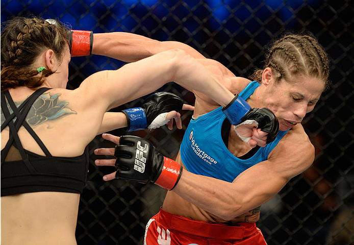 FORT CAMPBELL, KENTUCKY - NOVEMBER 6:  (L-R) Alexis Davis punches Liz Carmouche in their UFC women's bantamweight bout on November 6, 2013 in Fort Campbell, Kentucky. (Photo by Jeff Bottari/Zuffa LLC/Zuffa LLC via Getty Images) *** Local Caption ***Liz Carmouche; Alexis Davis
