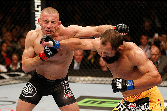 LAS VEGAS, NV - NOVEMBER 16:  (L-R) Georges St-Pierre exchanges punches with Johny Hendricks in their UFC welterweight championship bout during the UFC 167 event inside the MGM Grand Garden Arena on November 16, 2013 in Las Vegas, Nevada. (Photo by Josh Hedges/Zuffa LLC/Zuffa LLC via Getty Images) *** Local Caption *** Georges St-Pierre; Johny Hendricks