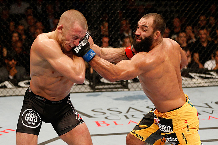 LAS VEGAS, NV - NOVEMBER 16:  (R-L) Johny Hendricks punches Georges St-Pierre in their UFC welterweight championship bout during the UFC 167 event inside the MGM Grand Garden Arena on November 16, 2013 in Las Vegas, Nevada. (Photo by Josh Hedges/Zuffa LLC/Zuffa LLC via Getty Images) *** Local Caption *** Georges St-Pierre; Johny Hendricks