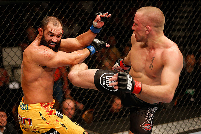 LAS VEGAS, NV - NOVEMBER 16:  (R-L) Georges St-Pierre kicks Johny Hendricks in their UFC welterweight championship bout during the UFC 167 event inside the MGM Grand Garden Arena on November 16, 2013 in Las Vegas, Nevada. (Photo by Josh Hedges/Zuffa LLC/Zuffa LLC via Getty Images) *** Local Caption *** Georges St-Pierre; Johny Hendricks