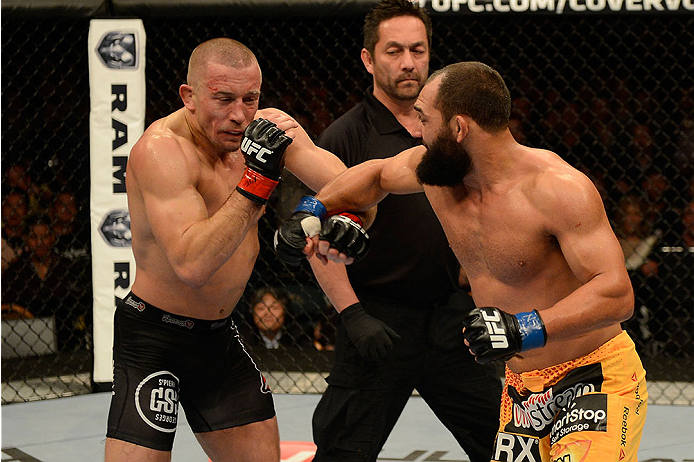 LAS VEGAS, NV - NOVEMBER 16:  (R-L) Johny Hendricks punches Georges St-Pierre in their UFC welterweight championship bout during the UFC 167 event inside the MGM Grand Garden Arena on November 16, 2013 in Las Vegas, Nevada. (Photo by Donald Miralle/Zuffa LLC/Zuffa LLC via Getty Images) *** Local Caption *** Georges St-Pierre; Johny Hendricks