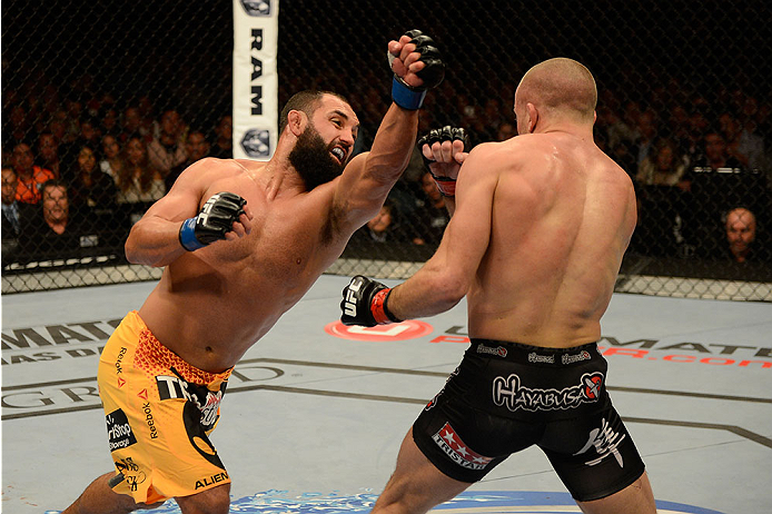 LAS VEGAS, NV - NOVEMBER 16:  (L-R) Johny Hendricks punches Georges St-Pierre in their UFC welterweight championship bout during the UFC 167 event inside the MGM Grand Garden Arena on November 16, 2013 in Las Vegas, Nevada. (Photo by Donald Miralle/Zuffa LLC/Zuffa LLC via Getty Images) *** Local Caption *** Georges St-Pierre; Johny Hendricks