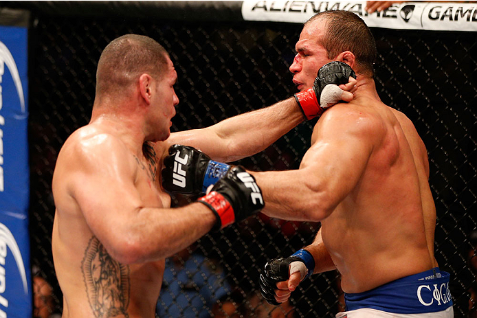 HOUSTON, TEXAS - OCTOBER 19:  (L-R) Cain Velasquez punches Junior Dos Santos in their UFC heavyweight championship bout at the Toyota Center on October 19, 2013 in Houston, Texas. (Photo by Josh Hedges/Zuffa LLC/Zuffa LLC via Getty Images)