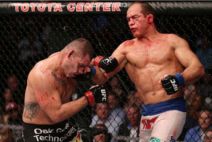 HOUSTON, TEXAS - OCTOBER 19:  (R-L) Junior Dos Santos punches Cain Velasquez in their UFC heavyweight championship bout at the Toyota Center on October 19, 2013 in Houston, Texas. (Photo by Nick Laham/Zuffa LLC/Zuffa LLC via Getty Images)